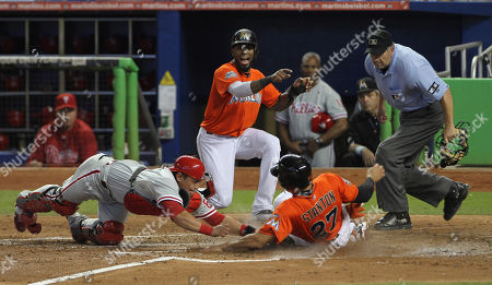 Giancario Stanton, Carlos Ruiz Miami Marlins player Jose Reyes and home plate umpire Dale Scott watch as Philadelphia Phillies catcher Carlos Ruiz (51) tags Marlins runner Giancario Stanton (27) out at home during the fourth inning of a MLB baseball game in Miami