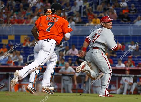 Carlos Ruiz, Jose Reyes Philadelphia Phillies' Carlos Ruiz (51) looks over his shoulder before being tagged out by Miami Marlins' Jose Reyes (7) in a rundown during the eighth inning of a baseball game in Miami, . The Phillies won 4-1