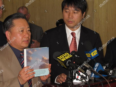 The Rev. Man Ho Lee holds up a book of photographs and poems during a press conference, in Mineola, N.Y. Lee was speaking after a court hearing in which he was designated as a health proxy for his terminally ill 28-year-old daughter, Sungeun Grace Lee. The decision to name the pastor as his daughter's health proxy ends what had been a court fight between the parents and the young woman. Family spokesman and Korean interpreter Jay Kim looks on at right