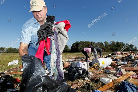 Stock Photo of Tom Metcalf Pastor Tom Metcalf collects clothes from the remains of Gladys Berry's mobile home in Anguilla, Miss., following a night and early morning of severe weather that destroyed several homes in this Delta community and sent some of its residents to area hospitals. Metcalf, his wife Jennifer and two deacons from their church, Straight Bayou Baptist Church in Anguilla, joined Berry's family and friends in trying to recover as many of her unbroken possessions as they could