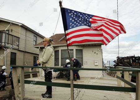 Stock Picture of Margret Anne Blair stands on her porch in Breezy Point as firemen help her with her home, after a fire caused by superstorm Sandy destroyed nearly 100 homes in the New York neighborhood