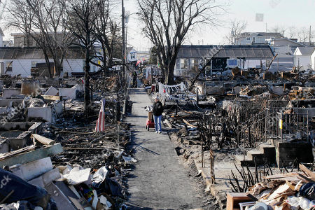 Louise McCarthy carting belongings from her flood-damaged home as she passes the charred ruins of other homes in the Breezy Point section of the Queens borough of New York. A fire leveled 130 houses in the beachfront community during Superstorm Sandy