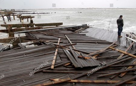 Stock Picture of Nicholas Rodriguez looks over a section of the destroyed boardwalk in Atlantic City, N.J., not far from where a powerful storm that started out as Hurricane Sandy made landfall the night before. Millions of people from Maine to the Carolinas awoke Tuesday without electricity, but the full extent of the damage in New Jersey, where the storm roared ashore Monday night with hurricane force, was unclear