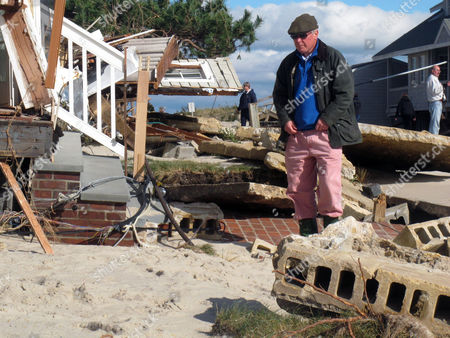 Peter Green looks at the wreckage of his oceanfront home in Bay Head, N.J. on . He says youths stole golf clubs from the ruins of his home on a stretch of Jersey shore that was devastated by Hurricane Sandy