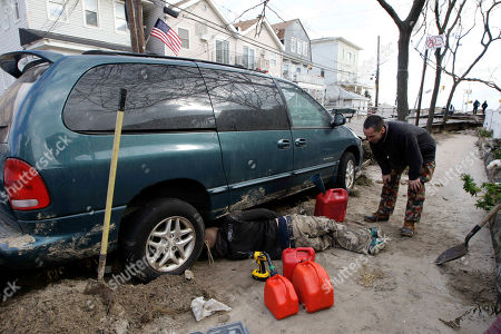Liam Thomas, right, watches as a friend extracts gasoline from an approving neighbor's vehicle, in Rockaway section of New York. More New Yorkers awoke Saturday to power being restored for the first time since Superstorm Sandy pummeled the region, but patience wore thin among those in the region who have been without power for most of the week