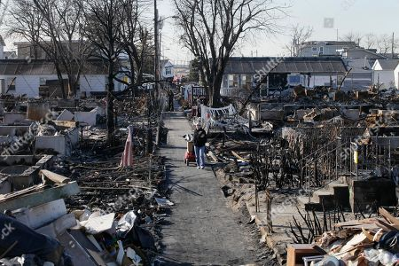 Louise McCarthy carting belongings from her flood-damaged home as she passes the charred ruins of other homes in the Breezy Point section of the Queens borough of New York. In the beachfront enclave of Breezy Point fire burned 130 houses and flooding destroyed another 220 during Superstorm Sandy