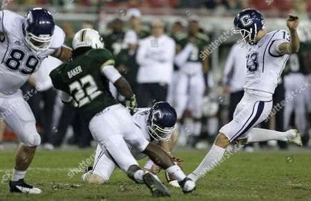 John Delahunt, Greg Baker, Chad Christen, Cole Wagner Connecticut kicker Chad Christen (13) boots a third-quarter field goal as Cole Wagner (86) holds during an NCAA college football game against South Florida, in Tampa, Fla. Connecticut's John Delahunt (89) blocks South Florida's George Baker (22
