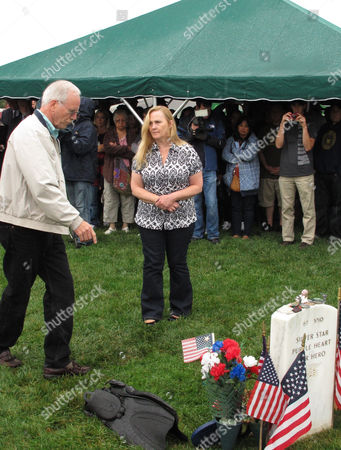 In this Oct. 2, 2012 photo, Daniel, left, and Maureen Murphy, the parents Navy SEAL Lt. Michael Murphy attend a memorial service at the gravesite for their son at at Calverton National Cemetery in Calverton, N.Y. The memorial service was attended by crew from the USS Michael Murphy, a Navy destroyer named for the Medal of Honor recipient killed in Afghanistan in 2005. The ship will be commissioned at a ceremony in New York City on