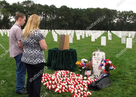 John Murphy and his mother, Maureen Murphy pray at the gravesite of their brother and son, Navy SEAL Lt. Michael Murphy following a memorial service at Calverton National Cemetery in Calverton, N.Y. The memorial service was attended by crew from the USS Michael Murphy, a Navy destroyer named for the Medal of Honor recipient killed in Afghanistan in 2005