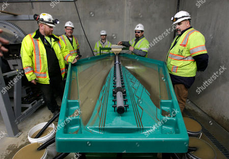 Matt Collins, chief operating officer of the Sutter Gold Mining Co., left, watches as Allen Smith, second from left, Brain Herfel, third from left, Ted Chapman fouth from left, and Wayne Murphy, right, calibrate the water flow of a gravity table at the company's newly constructed mill near Sutter Creek, Calif. The gravity table uses technology similar to those used by gold rush-era miners who used pans to separate gold from surrounding materials. The company, which has begun mining adjacent to the historic Comet-Lincoln ore zones, announced Monday, Dec. 17, 2012, that it poured its first gold as it prepared to begin the first large scale Sierra Nevada underground gold mining in a half century