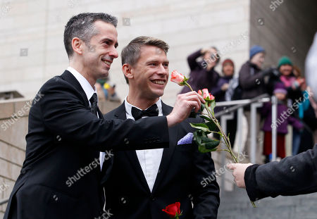 Dan Savage, left, and his husband Terry Miller are handed flowers after their wedding at Seattle City Hall, in Seattle. Gov. Chris Gregoire signed a voter-approved law legalizing gay marriage Wednesday, Dec. 5 and weddings for gay and lesbian couples began in Washington state on Sunday, following the three-day waiting period after marriage licenses were issued earlier in the week