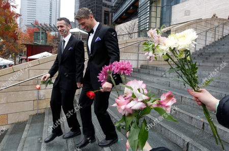 Dan Savage, left, and his husband Terry Miller walk past well-wishers after wedding at Seattle City Hall, becoming among the first gay couples to legally marry in the state, in Seattle. Gov. Chris Gregoire signed a voter-approved law legalizing gay marriage Dec. 5 and weddings for gay and lesbian couples began in Washington state on Sunday, following the three-day waiting period after marriage licenses were issued earlier in the week