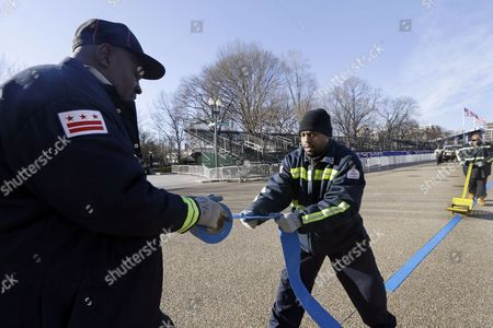 Charles King, left, and Mark Johnson, right, make preparations for the 57th Inauguration weekend of events near the White House in Washington
