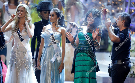 Irene Sofia Esser Quintero, Renae Ayris, Janine Tugonon Miss Venezuela, Irene Sofia Esser Quintero, right, reacts as a hair stylist touches up her hair with hairspray while waiting during a commercial break with Miss Australia, left, Renae Ayris, and Miss Philippines Janine Tugonon, during the Miss Universe pageant, in Las Vegas