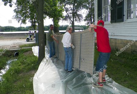 Stock Picture of Three generations of the Bankhead family prepare to place a canvass wall around a historic home built in 1850 by their ancestors, in Clarksville, Mo. Thomas Bankhead, middle, lives in home. His cousin, Reid, left, and his grandson, Alex, right, were lifting up the wall, with plans to later add sand in the middle as protection from the surging Mississippi River a short distance away