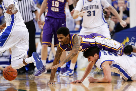Anthony James, Avery Dingman Northern Iowa's Anthony James leaps over Creighton's Avery Dingman as they chase a loose ball in the second half of an NCAA college basketball game in Omaha, Neb., . Creighton won 79-68