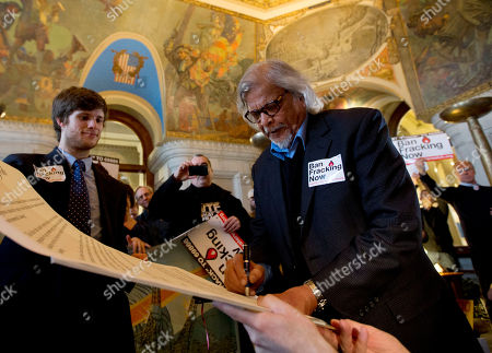 """Arun Gandhi, Daniel Morrissey Arun Gandhi, grandson of nonviolent protest leader Mahatma Gandhi, signs a pledge resisting hydraulic fracturing, or fracking, during a rally in the War Room at the Capitol, in Albany, N.Y. Earlier during a joint budget hearing on the environment, Commissioner Joe Martens of the New York State Department of Environmental Conservation said his agency has no """"timetable"""" for finishing shale gas drilling rules, with the completion date dependent on recommendations made by the health commissioner. Daniel Morrissey, left, holds the document"""
