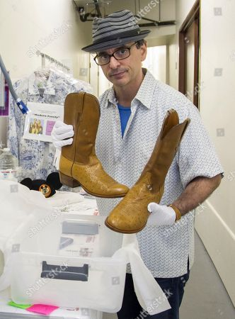 """James Comisar James Comisar shows boots worn by actor Larry Hagman as oil tycoon J. R. Ewing in the TV show """"Dallas."""" The item is part of his television memorabilia collection in a temperature- and humidity-controlled warehouse in Los Angeles"""