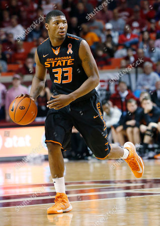 "Oklahoma State guard Marcus Smart (33) dribbles against Oklahoma during an NCAA college basketball game in Norman, Okla., . The Oklahoma State players are wearing an orange ribbon on their uniforms that says ""Patsy"" in memory of Patsy Sutton, who died recently. She was the wife of former OSU coach Eddie Sutton"