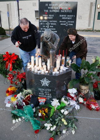 Topeka Police Lt. Jack Mackey, left, and Jennifer Walker light candles in honor of two officers killed in the line of duty in Topeka, Kan., . A man with a history of theft and weapons convictions gunned down two police officers investigating possible drug activity in a Kansas grocery parking lot, and was later killed after an armed standoff, authorities said Monday