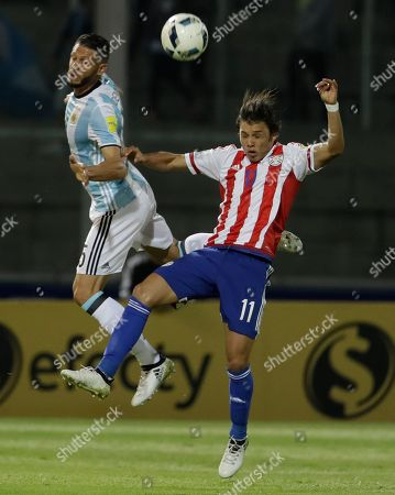 Argentina's defender Martin Demichelis, left, and Paraguay's forward Angel Romero vie for the ball during a 2018 World Cup qualifying soccer match in Cordoba, Argentina
