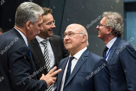 Luxembourg's Finance Minister Pierre Gramegna, right, talks with Dutch Finance Minister and chair of the eurogroup finance ministers Jeroen Dijsselbloem, 2nd left, while France's Finance Minister Michel Sapin, 2nd right, talks with Austria's Finance Minister Hans Jorg Schelling during an Eurogroup meeting at the EU Council in Luxembourg on . EU Economy Commissioner Pierre Moscovici says Greece has met all outstanding conditions required to receive more funds to bolster its debt-strapped economy
