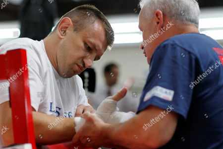 Stock Photo of Tomasz Adamek, Roger Bloodworth Polish heavyweight boxer Tomasz Adamek, left, has his hands taped by trainer Roger Bloodworth as he prepares to work out at the World Boxing and Fitness Center in Jersey City, N.J., . Adamek will fight Travis Walker September 8, 2012, at Newark's Prudential Center