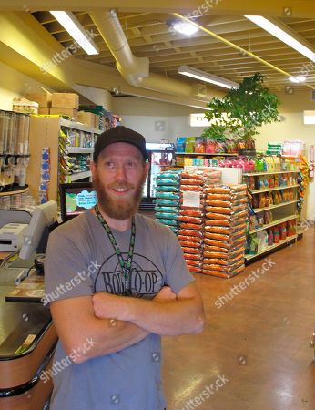 In this photo made, Boise Co-op pet food buyer Zach Jones poses in Boise, Idaho in the store's new space dedicated to natural pet food and supplies. Opening up a separate storefront for the fast-growing pet food segment is one of the ways the 39-year-old co-op is gearing up for increased competition from Whole Foods Market, which opens in Boise in October