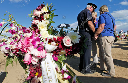 """Terry Jones, Ginger Sanders, Toni New Aurora Deputy Police Chief Terry Jones, left, prays with Ginger Sanders, from Gadsden, Ala., and Toni New, from Kingsport, Tenn., at the memorial across from the movie theater, in Aurora, Colo. Twelve people were killed and over 50 wounded in a shooting attack early Friday at the packed theater during a showing of the Batman movie, """"The Dark Knight Rises"""