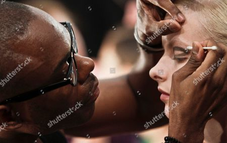 Stock Image of Fashion stylist Antwone Urquhart, left, outline the eyes of Elza Luijendijk, a model from Holland, for the look she will wear in the show for the Spring 2013 collection of Richard Chai on in New York