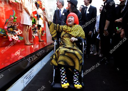 Yayoi Kusama, Yves Carcelle Artista Yayoi Kusama, center poses for photographers with Louis Vuitton CEO Yves Carcelle, upper left, in front of the windows of Vuitton's flagship store for the unveiling of a new collaborative collection by Vuitton creative designer Marc Jacobs and Kusama in New York