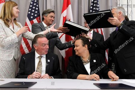 Lisa P. Jackson, Peter Kent Canada's Minister of the Environment Peter Kent, seated left, and EPA Administrator Lisa Jackson, seated right, talk as Great Lakes Water Quality agreements are swapped for signing during a ceremony at the Canadian Embassy in Washington