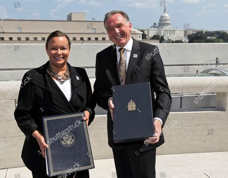 Lisa P. Jackson, Peter Kent With the Capitol dome in the background, EPA Administrator Lisa Jackson, left, and Canada's Minister of the Environment Peter Kent, hold copies of an updated Great Lakes Water Quality Agreement during a photo opportunity before a signing ceremony, at the Canadian Embassy in Washington