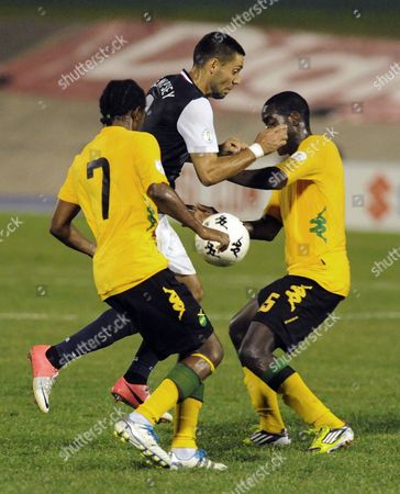 United States' Clint Dempsey, center, is challenged by Jamaica's Jason Morrison, left, and Jevaughn Watson during a 2014 World Cup qualifying soccer match in Kingston, Jamaica