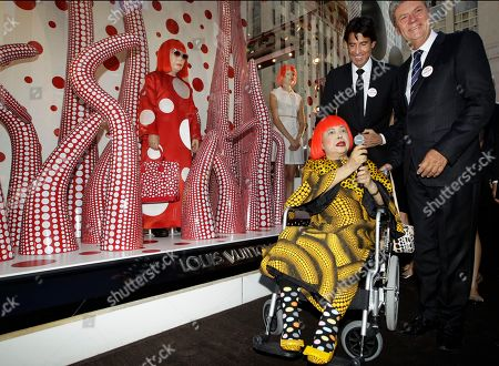 Stock Photo of Yayoi Kusama, Yves Carcelle, Jordi Konstans Japanese artist Yayoi Kusama in a red wig speaks with Louis Vuitton's second in command Jordi Konstans, left, and CEO Yves Carcelle, right, in front of the windows of Vuitton's flagship store for the unveiling of a new collaborative collection by Vuitton creative designer Marc Jacobs and Kusama in New York. Kusama's signature splash of dots has now arrived in the realm of fashion in a new collection from French luxury brand Louis Vuitton - bags, sunglasses, shoes and coats. The latest Kusama collection is showcased at its boutiques around the world, including New York, Paris, Tokyo and Singapore, sometimes with replica dolls of Kusama