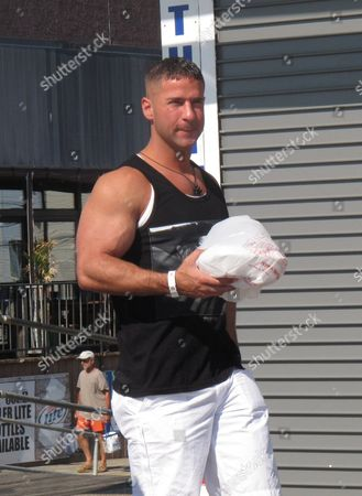 """This photo shows """"Jersey Shore"""" cast member Mike """"The Situation"""" Sorrentino carrying breakfast out of a restaurant on the Seaside Heights, N.J. boardwalk as filming of the the MTV series was winding down its sixth season. The network says the cast wrapped up filming with a group hug at the end of the July 4th holiday weekend. Sorrentino, Nicole """"Snooki"""" Polizzi, Jenny """"JWoww"""" Farley, Deena Nicole Cortese, Vinny Guadagnino, Paul """"Pauly D"""" DelVecchio, Samantha Giancola and Ronnie Ortiz-Magro then loaded their luggage and drove off. MTV says Season 6 will feature Cortese's arrest after she was dancing in the streets. She pleaded guilty to failing to use the sidewalk"""