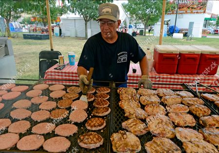Steve Wright Steve Wright, with the Kentucky Pork Producers Association, flips pork burgers during the opening day of the Kentucky State Fair, in Louisville, Ky. The State Fair runs through the 26th