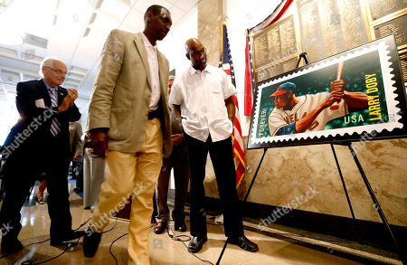 Larry Doby Jr., Bill Pascrell, Jeffery Jones Larry Doby, Jr., right, the son of the first black baseball player to play in the American League, looks at a commemorative U.S. postage stamp in honor of his father, Larry Doby, in Paterson, N.J. Standing next to Doby Jr. are congressman Bill Pascrell, left, and Paterson Mayor Jeffery Jones during the stamp release celebration. The South Carolina-born Doby attended Eastside High School in Paterson, where he earned 11 varsity letters in several different sports. The Hall of Famer began his professional baseball career with the Newark Eagles of the Negro National League. After serving in World War II, Doby returned to the Eagles before joining the Cleveland Indians in 1947