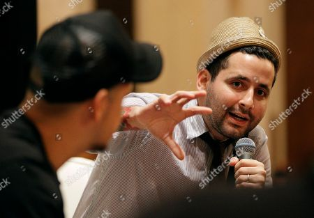 Rene Perez, Eduardo Jose Cabra Residente, left, also known as Rene Perez, listens as Visitante, (Eduardo Jose Cabra), of the Puerto Rican musical group Calle 13, speaks during a panel discussion with the Latin Recording Academy's Gabriel Abaroa (not shown) at the Latin Alternative Music Conference in New York