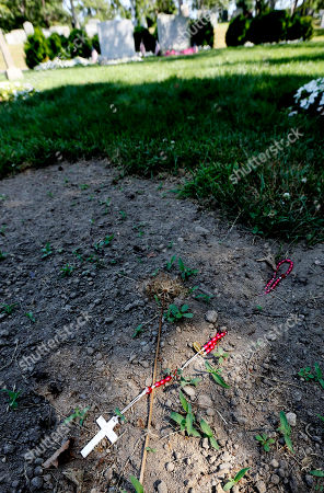 Rosary beads lie on the soil at the site where Mary Richardson Kennedy was originally interred near the twin grave stones of Sargent Shriver and Eunice Kennedy Shriver, top center, in Saint Francis Xavier Cemetery in Centerville, Mass., . Seven weeks after her suicide, Mary Richardson Kennedy was reburied in a Cape Cod cemetery 700 feet from her original grave near other Kennedy family members