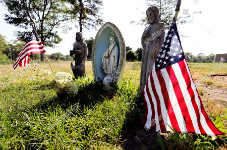 Religious statues and American flags stand at the grave site to which Mary Richardson Kennedy's body was moved in Saint Francis Xavier Cemetery in Centerville, Mass. on . Seven weeks after her suicide, Mary Richardson Kennedy was reburied in the Cape Cod cemetery 700 feet from her original grave near other Kennedy family members