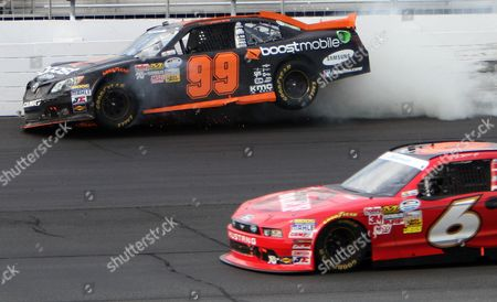 Ricky Stenhouse Jr. (6) drives low as Travis Pastrana hits the wall during the NASCAR Nationwide Series auto race, at New Hampshire Motor Speedway in Loudon, N.H. Bred Keselowski won the race