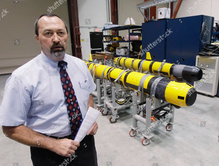 Stock Photo of Christopher Egan, an unmanned systems customer advocate, stands near a pair of unmanned underwater vehicles (UUV) in a lab at the Naval Undersea War Center in Middletown, RI., . Narragansett Bay is the testing ground for the Naval Undersea Warfare Center where the Navy is working toward its goal of achieving a squadron of self-driven, undersea vehicles