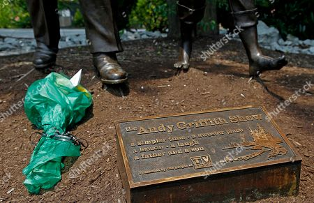 A bouquet of flowers rest at the foot of an Andy and Opie Taylor statue near the Andy Griffith Playhouse in Mount Airy, N.C., . The iconic actor and North Carolina native died Tuesday at the age of 86