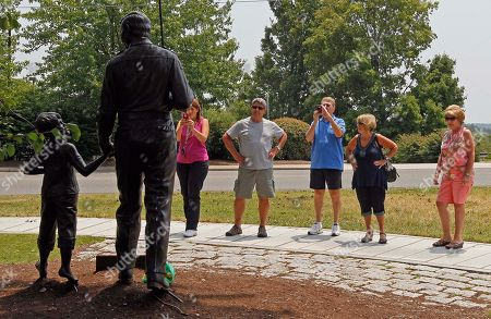 People gather around a statue of Andy and Opie Taylor at the Andy Griffith Playhouse in Mount Airy, N.C., . The iconic actor and North Carolina native died Tuesday at the age of 86