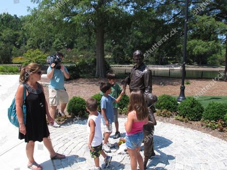 Patrice Graham and her grandchildren visit a statue of Andy Griffith at Pullen Park in Raleigh, N.C., on . The iconic actor and North Carolina native died Tuesday at the age of 86