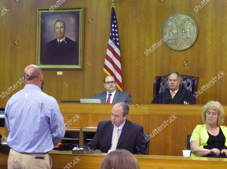"Stock Picture of Former Saluda County Sheriff Jason Booth, left, tells the people of his county he is sorry as Judge Doyet ""Jack"" Early III, seated at upper right, listens during Booth's guilty plea to a misconduct in office charge at the Aiken County Courthouse in Aiken, S.C., on . Booth was sentenced to probation after admitting he used an inmate to build a party shed, ornate gate and other items at his home in exchange for letting the prisoner live outside the jail and have conjugal visits with his girlfriend"