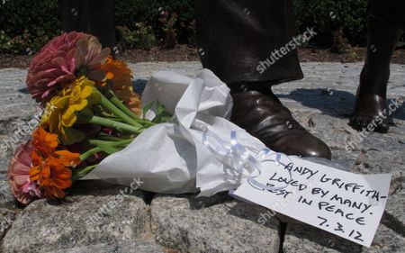 A bouquet of flowers at the foot of a statue of Andy Griffith at Pullen Park in Raleigh, N.C. Tourism in Mount Airy is up since Andy Griffith died July 3, with about 10,400 people visiting the Andy Griffith Museum in July, almost double the 5,400 who visited in July 2011