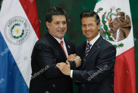 Enrique Pena Nieto, Horacio Cartes Jara Paraguay's President Horacio Cartes, left, and Mexican President Enrique Pena Nieto, shake hands following the signing of documents and a joint statement to the press, at the National Palace in Mexico City