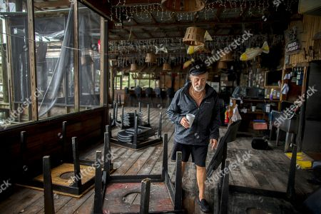 Crab Shack restaurant owner Jack Flanagan walks through the dining area of his business near Tybee Island, Ga., after winds and storm surge from Hurricane Matthew hit the small community along the east coast of Georgia